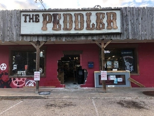 The Bike Peddler, Austin. A red brick building where the front door has been blown open.